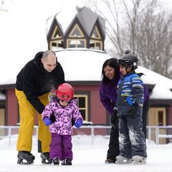 Une famille de 4 (2 parents and 2 jeunes enfant) qui patinent.  Le pavillon d'hiver est en arrière-plan.
