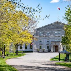 View of driveway leading up to Rideau Hall. Trees in bloom on either side.