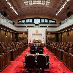 Empty Senate of Canada chamber. Several dark desks down the middle aisle. Dark brown leather chairs in seating areas on either side. A large throne at the front of the room. A glass-balcony gallery looks down on the space.