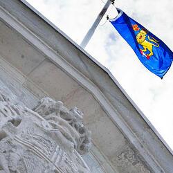 Vue sur le drapeau du gouverneur général au sommet de Rideau Hall. Ciel lumineux avec des nuages blancs.