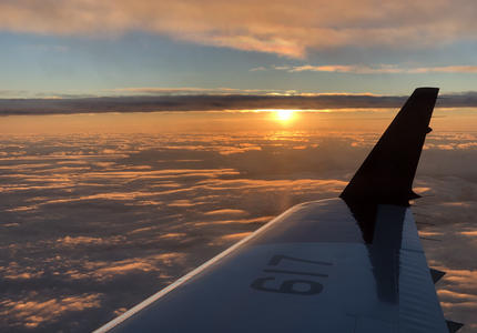 View of airplane wing from inside a plane with the sun setting.