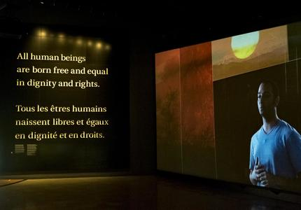 """On one wall a video is playing, on another wall the words """"All human beings are born free and equal in dignity and rights"""" are written."""