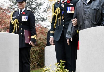 The Governor General of Canada, in a canadian army uniform, is stopping at a tomb in a cemetary with a veteran at her side.