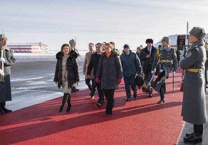 The Governor General walks on a red carpet which leads to the stairs of an airplane in the background.  She is surrounded by officials.  Armed guards line the red carpet.