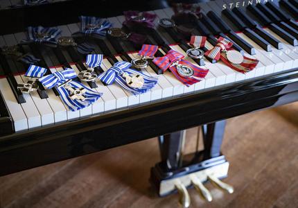 Une série de médailles sont placées sur le clavier d'un piano.