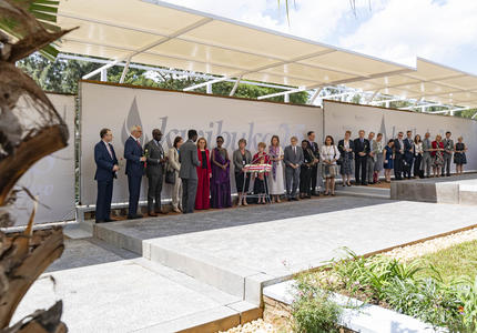 The Governor General and members of the Canadian delegation stand in a line at the Kigali Genocide Memorial.