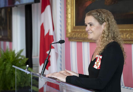 The Governor General delivers opening remarks at a podium.