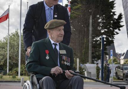 Un ancien combattant en fauteuil roulant, portant un béret et des médailles de guerre, est poussé par un homme. Plusieurs drapeaux sont en arrière-plan.