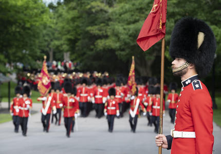 A guard stands at attention as the rest of the Ceremonial Guard make their way up the path towards Rideau Hall.