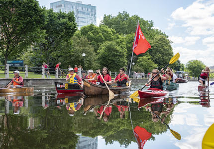 The Governor General is kayaking down the Ottawa canal and other people are accompanying her in canoes.
