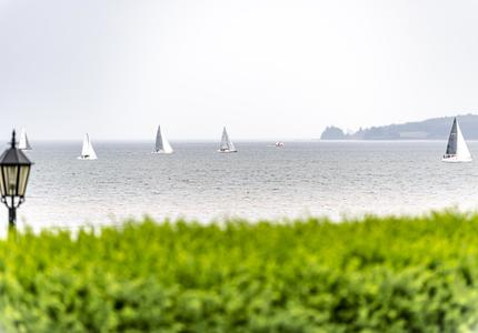 A photo of the ocean with sailboats in the distance.