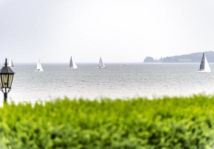 Une photo de l'océan avec des voiliers en arrière-plan.
