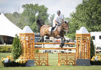 A rider and his horse jump over a fence during an outdoor equestrian competition.