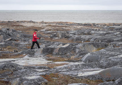 The Governor General is walking over rocky terrain.