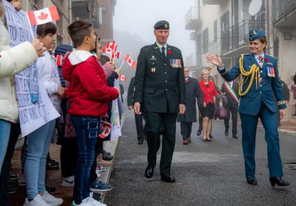 La gouverneure générale Julie Payette, vêtue de l'uniforme des Forces aériennes du Canada, salue des enfants portant de petits drapeaux canadiens sur un trottoir.