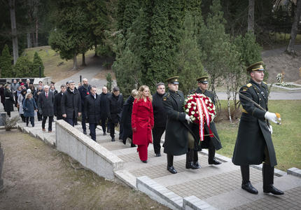 The Governor General and the delegation walk in a procession to the monument.