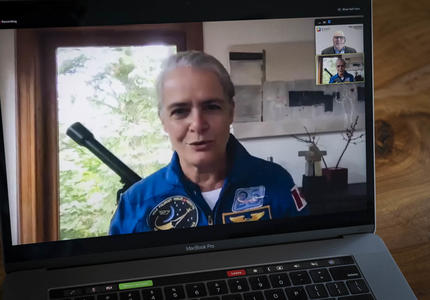 A woman in a blue space flight suit is shown on an open laptop screen.