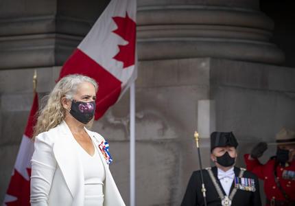 Une femme vêtue d'un costume blanc avec un masque noir est en train de marcher. Un homme en uniforme noir et un agent de la Gendarmerie royale du Canda portant un uniforme rouge saluent en arrière-plan. Il y a également deux drapeaux canadiens.