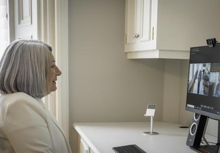 La gouverneure générale désignée Mary May Simon est assise à un bureau. Elle regarde un écran d'ordinateur sur lequel on peut voir Sa Majesté la Reine.