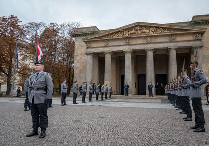 Grand bâtiment à l'arrière-plan. Des membres de l'armée allemande sont debout, en uniforme. Ils sont à l'extérieur.