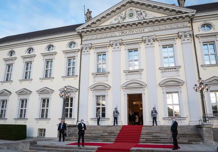Grand bâtiment blanc de style victorien avec un tapis rouge à l'extérieur. La porte d'entrée est ouverte. Il y a trois hommes en uniforme militaire et trois hommes en costume.