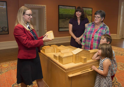 A guide-interpreter showing a group of four (2 women and 2 children) a model of Rideau Hall.