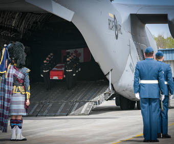 At the forefront, we see the back of Canadian Armed Forces(CAF) members, including a bagpiper. In the background, we see a coffin, carried by CAF members, being taken off a plane.