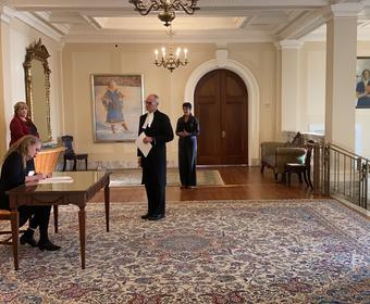The Governor General is sitting at a desk. On the right hand side, there is a man holding a document in his hands. Four other people are standing around the desk all while respecting the social distancing norms.
