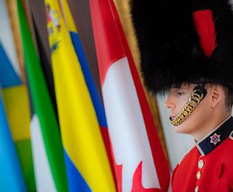A member of the Governor General's Foot Guards is standing in front of flags.