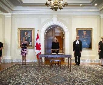Cinq personnes sont alignées contre un mur jaune pâle. Une table est devant la personne au centre. Un drapeau du Canada se trouve à sa droite.