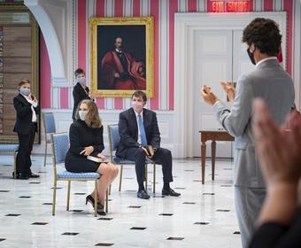 Un homme et une femme sont assis tandis qu'un petit nombre de spectateurs applaudissent.