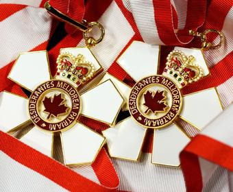 Two Order of Canada medals side by side with ribbons curled up.